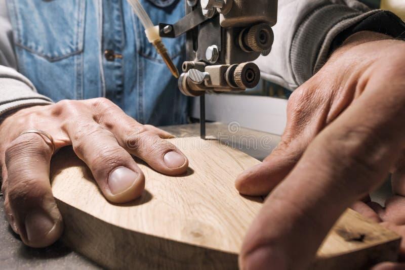 Constructor del carpintero del hombre joven que trabaja con el rompecabezas y la madera el?ctricos imagenes de archivo