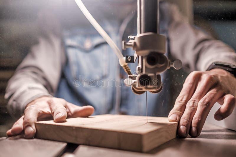 Constructor del carpintero del hombre joven que trabaja con el rompecabezas y la madera el?ctricos imagen de archivo
