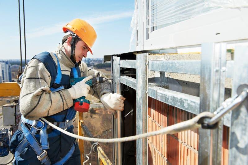 Constructor del trabajador en el trabajo de la instalación de la fachada foto de archivo libre de regalías