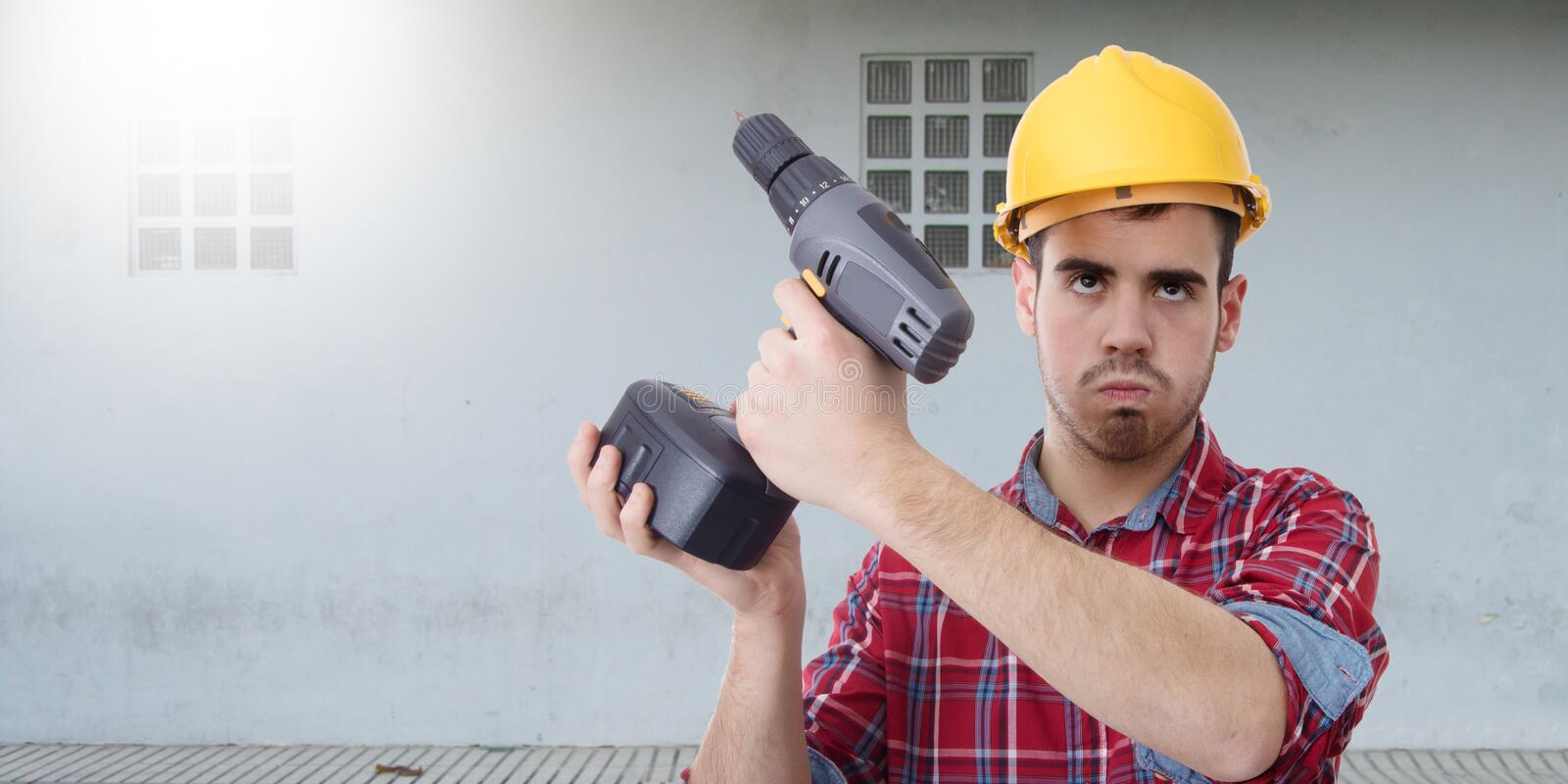 Constructor with drill. Renovations, repairs and bricolage royalty free stock photography