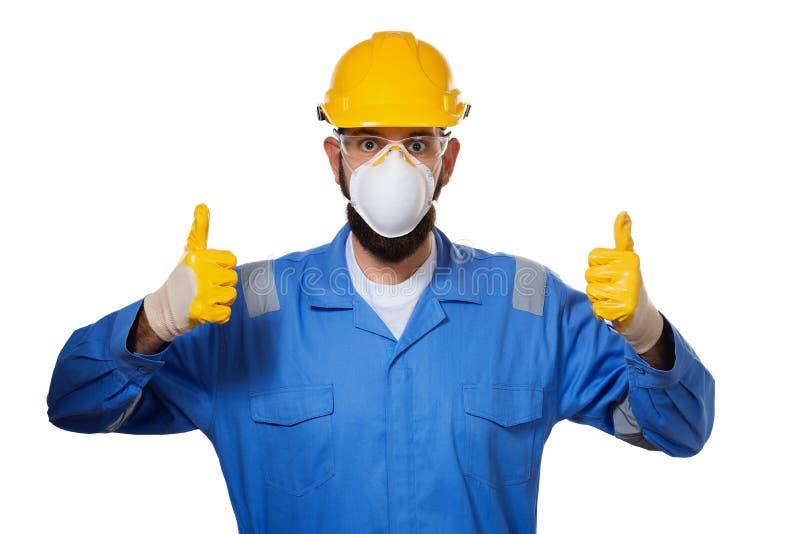 Constructor en casco en la máscara y las gafas de seguridad transparentes que aumentan sus pulgares para arriba en guantes de tra imágenes de archivo libres de regalías
