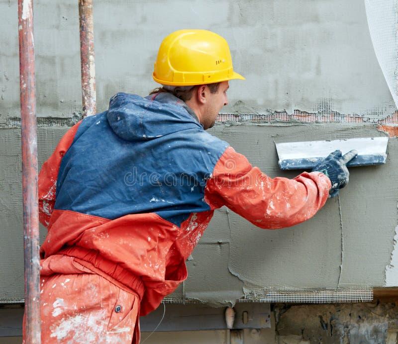 Constructor en la fachada que enyesa trabajos imagenes de archivo