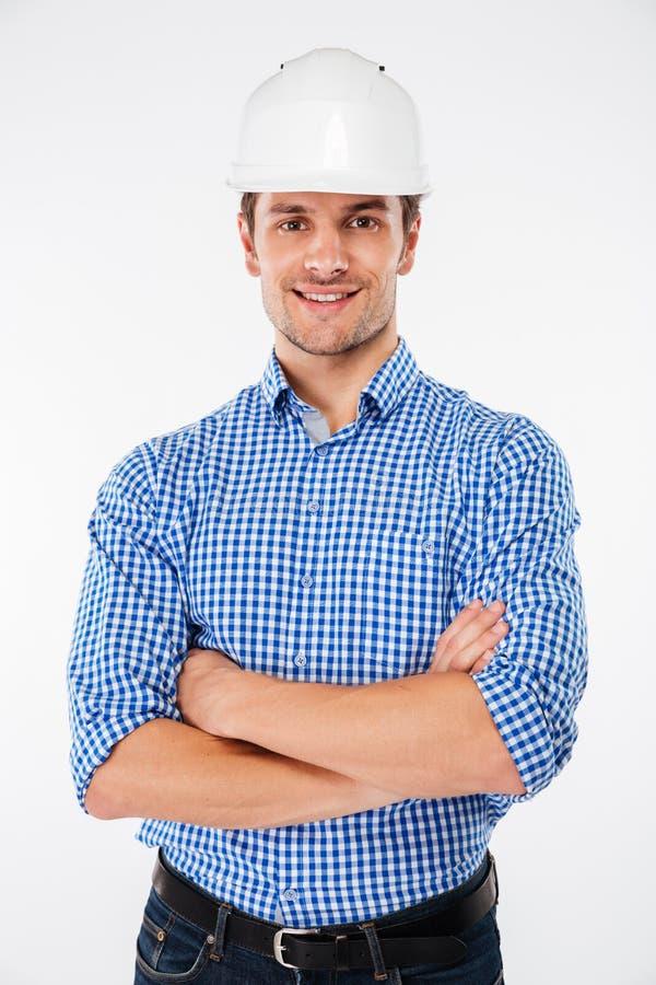 Constructor feliz del hombre en el casco que se coloca con los brazos cruzados foto de archivo