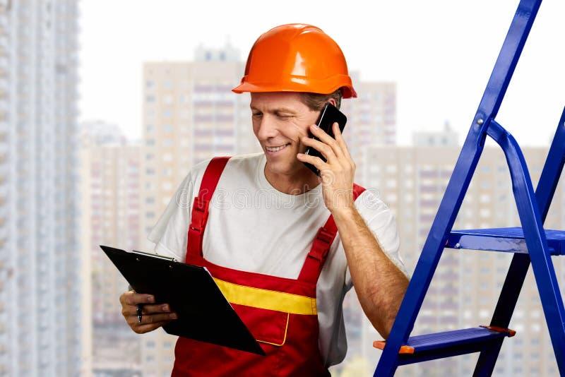 Constructor feliz que habla en el teléfono imagenes de archivo