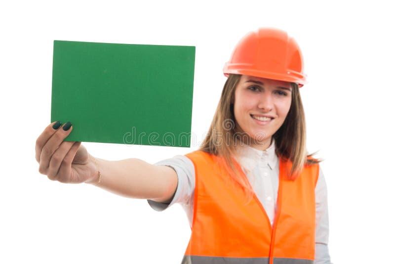 Constructor hermoso de la chica joven que muestra el papel en blanco foto de archivo libre de regalías