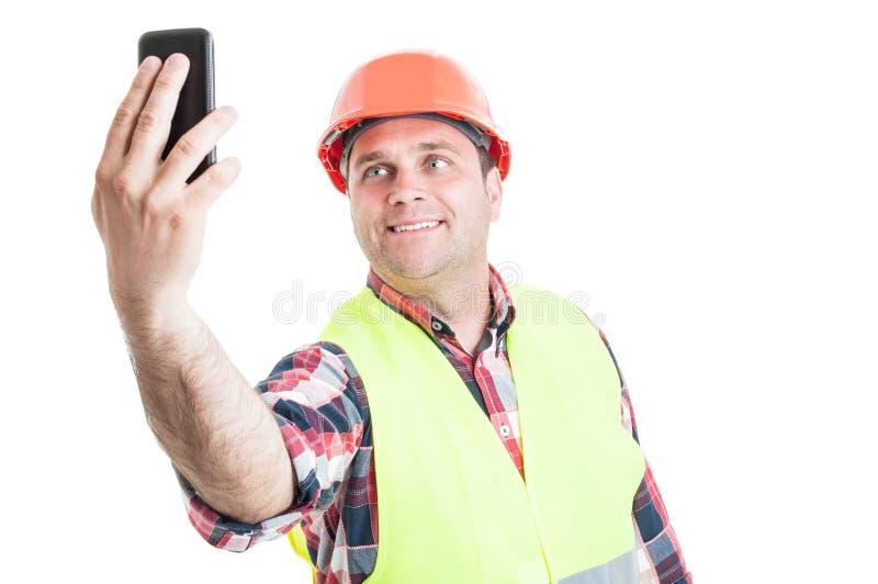 Constructor hermoso sonriente que hace el autorretrato imagen de archivo