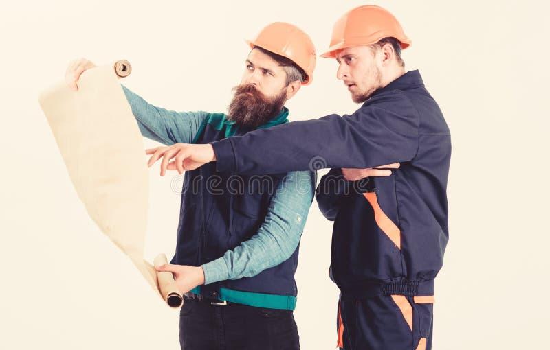 Constructor, ingeniero, trabajo del arquitecto sobre proyecto Hombres en cascos fotografía de archivo libre de regalías