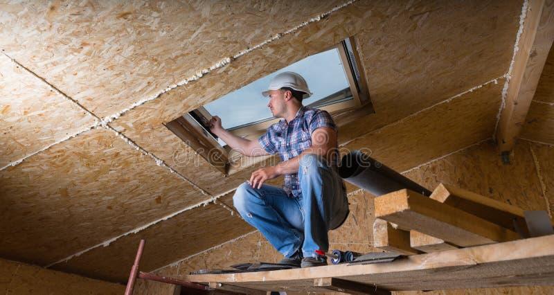 Constructor Inspecting Skylight en casa inacabada imagen de archivo