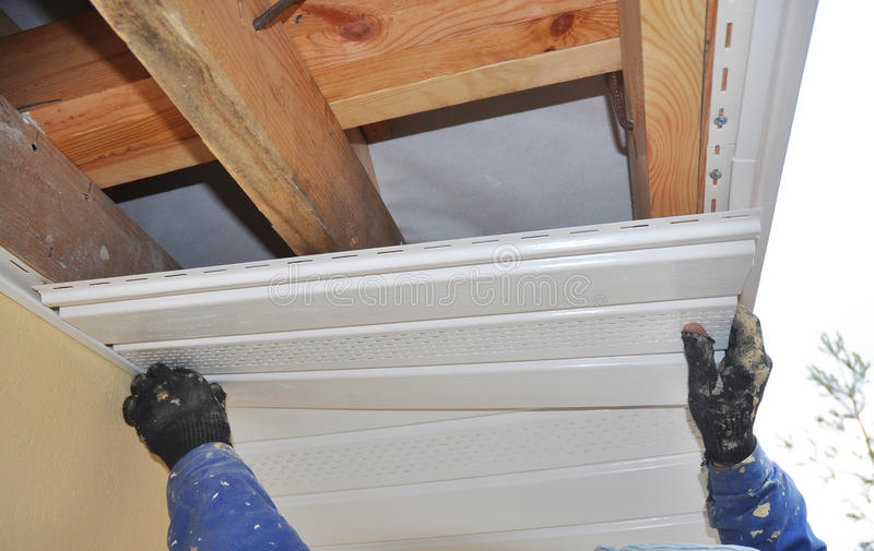 Constructor Install Soffit. Roofing Construction. Soffit and Fascia. Is Usually Constructed of Vinyl, Wood or Aluminum and is Installed on the Underside of Roof royalty free stock photography