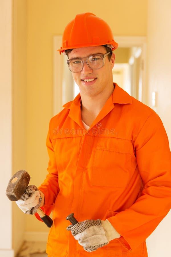 Constructor joven que sostiene el cincel foto de archivo