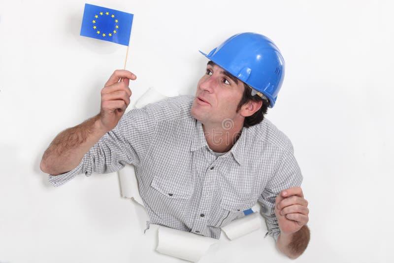 Constructor que agita un indicador europeo fotos de archivo libres de regalías