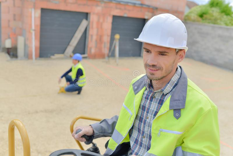Constructor que conduce el excavador o la retroexcavadora imágenes de archivo libres de regalías