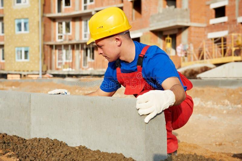 Constructor que instala el bordillo del concreto del camino fotos de archivo libres de regalías