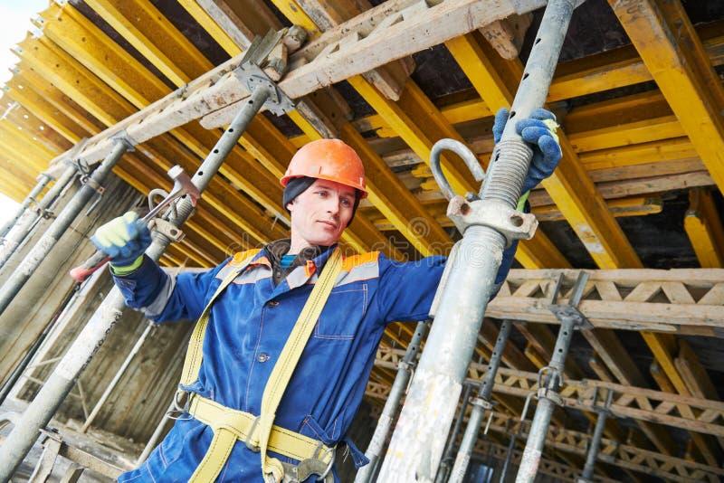 Constructor que instala o que desmonta la ayuda de polo para el encofrado monolítico concreto en la construcción inmobiliaria imágenes de archivo libres de regalías