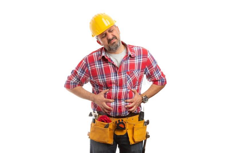 Constructor que lleva a cabo las manos en el estómago hinchado fotografía de archivo libre de regalías
