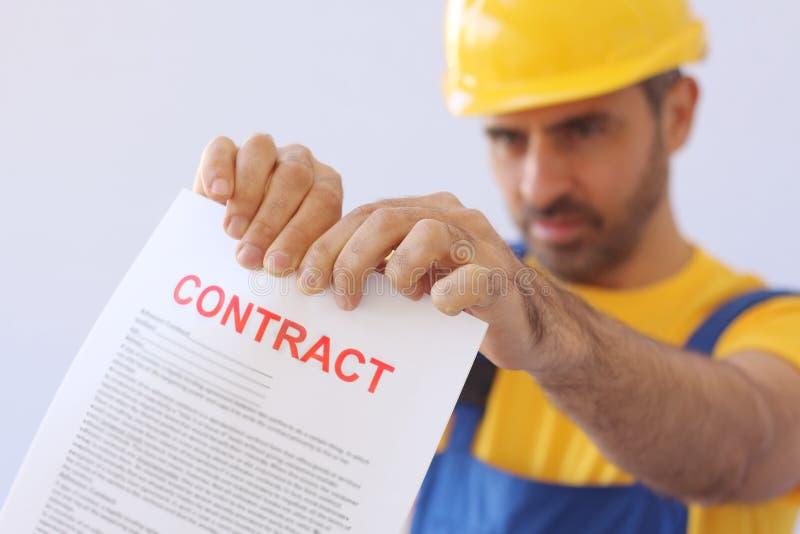 Constructor que rasga para arriba un contrato foto de archivo libre de regalías
