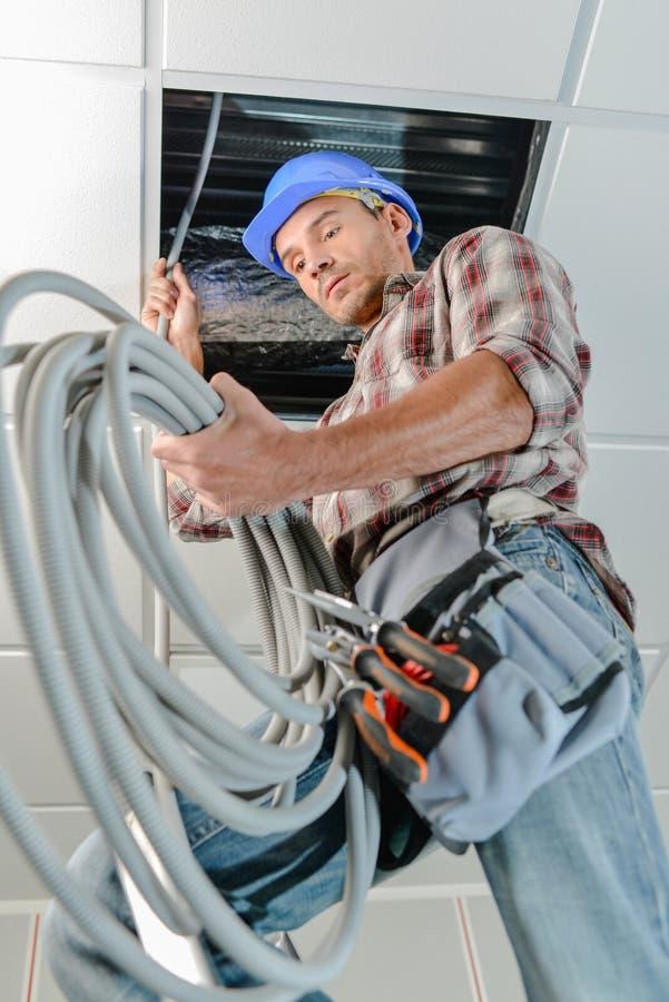 Constructor que rosca el cable en roofspace imagen de archivo