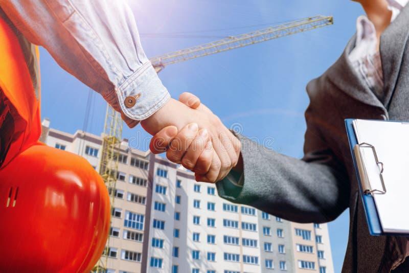 Constructor que sacude las manos con el hombre de negocios fotografía de archivo
