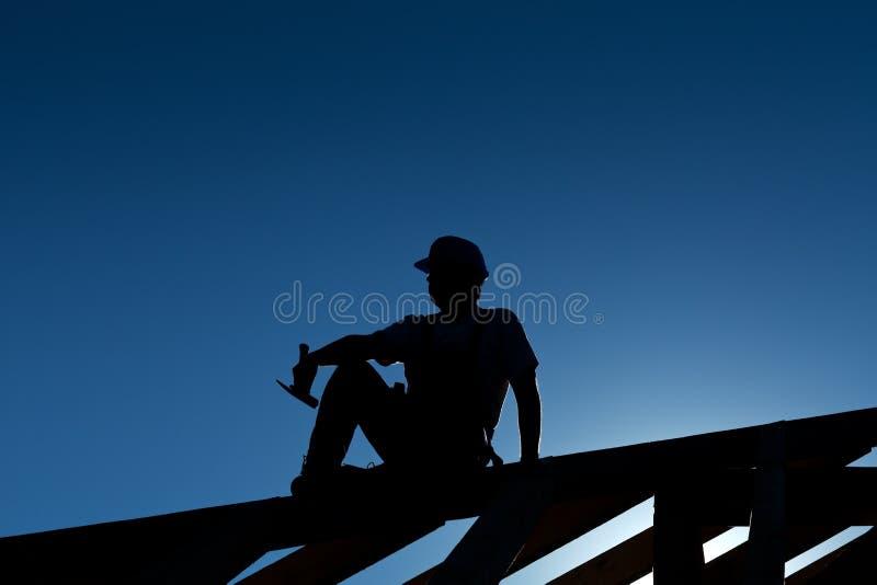 Constructor que se reclina encima de la estructura de azotea fotografía de archivo