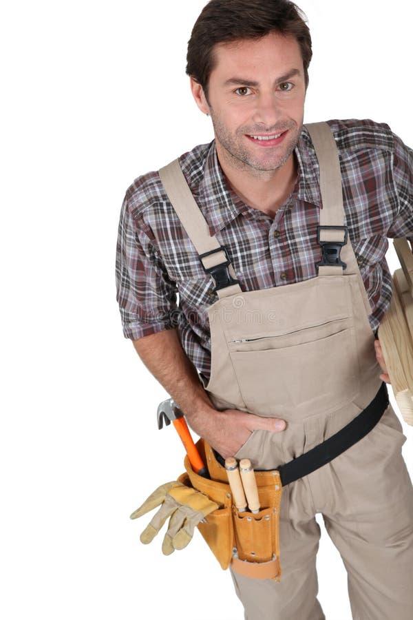 Constructor que sonríe con las herramientas. fotografía de archivo