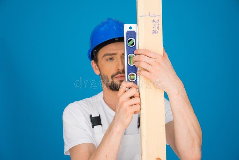 Constructor que sostiene un nivel de alcohol y un tablón de la madera imagen de archivo libre de regalías