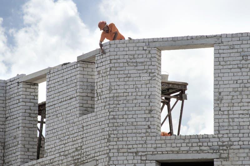 Constructor que trabaja en la construcción de la casa del ladrillo Ucrania, imagenes de archivo