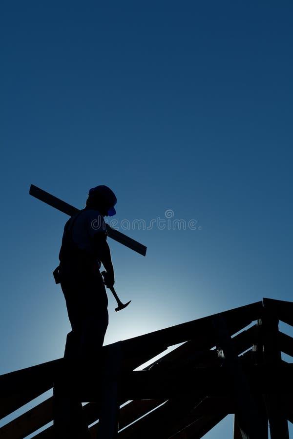 Constructor que trabaja tarde encima del edificio fotos de archivo