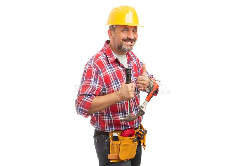 Constructor showing thumb-up as like gesture. Friendly constructor showing thumb-up as like gesture and holding hammer and wrench isolated on white background royalty free stock photo