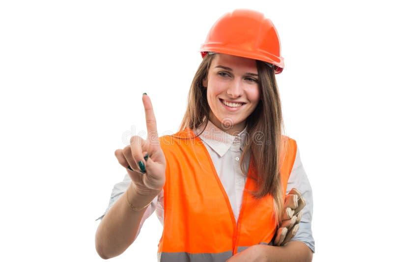 Constructor sonriente de la mujer que señala la pantalla virtual foto de archivo