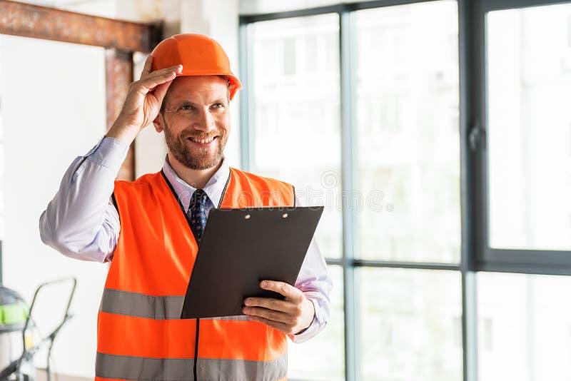 Constructor sonriente feliz que guarda documentos fotografía de archivo libre de regalías