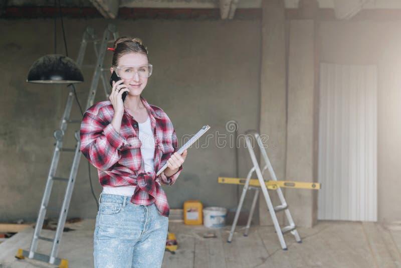 Constructor sonriente joven de la empresaria, ingeniero, arquitecto, diseñador en el taller, hablando en el teléfono celular fotos de archivo libres de regalías