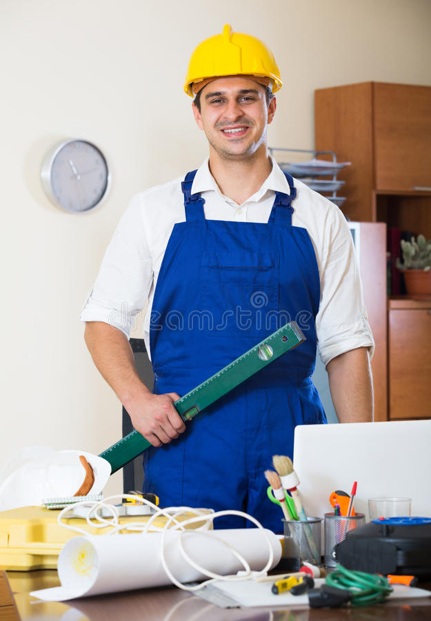 Constructor with tools and blueprints in office. Positive designer-constructor with tools and documentation at work place royalty free stock photo