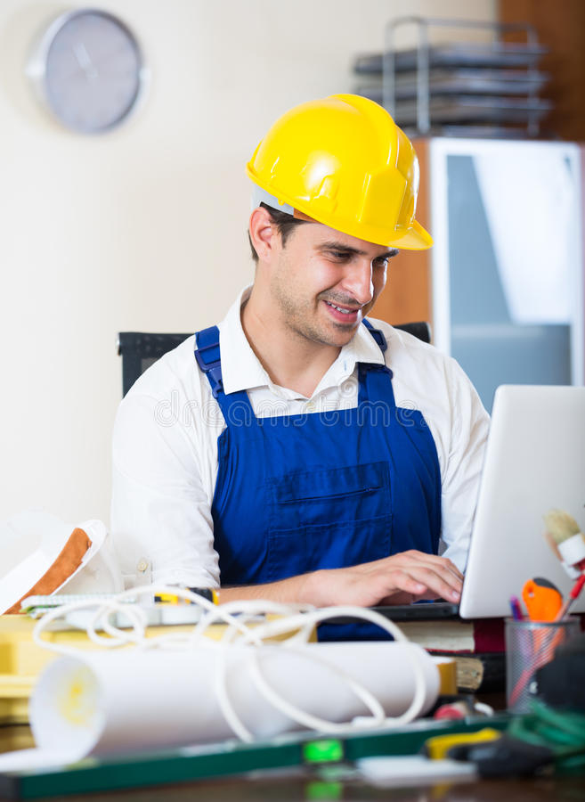 Constructor with tools and blueprints in office. Positive designer-constructor with tools and documentation at work place stock image