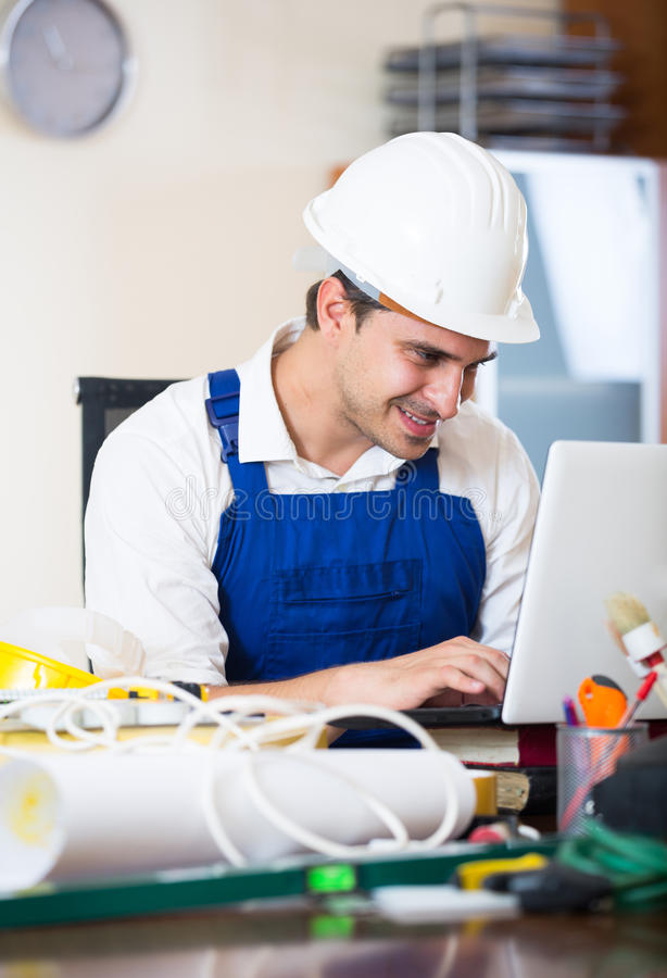 Constructor with tools and blueprints in office. Positive designer-constructor with tools and documentation at work place royalty free stock image