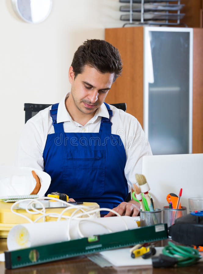 Constructor with tools and blueprints in office. Positive designer-constructor with tools and documentation at work place stock photos