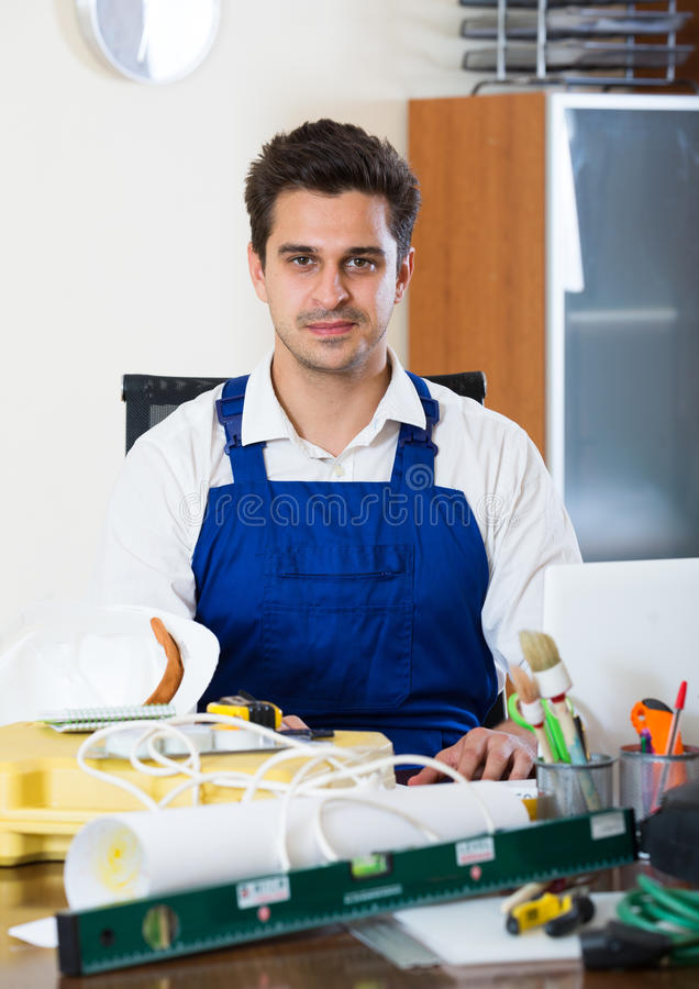 Constructor with tools and blueprints in office stock photo