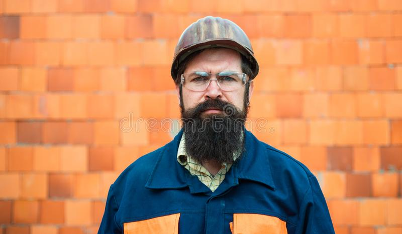 Constructor Trabajador mecánico del retrato Hombre barbudo en traje con el casco de la construcción Retrato del ingeniero hermoso imagenes de archivo