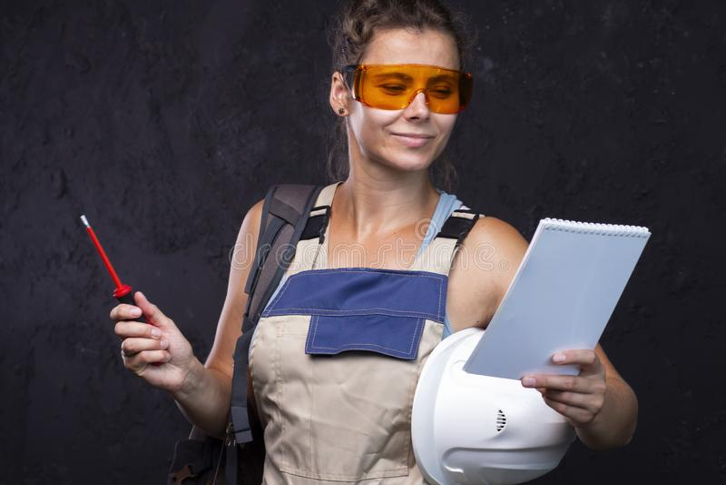 Constructor Woman Trabajador de sexo femenino en uniforme Emplazamiento de la obra Ingeniero del arquitecto con la lista de verif foto de archivo