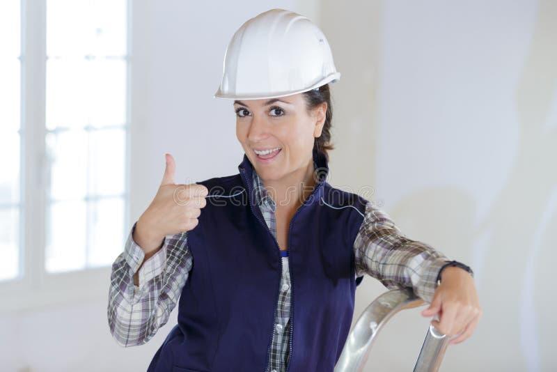 Constructora de una mujer con el pulgar arriba fotografía de archivo