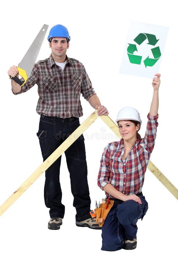 Constructores con una muestra del reciclaje imagen de archivo libre de regalías