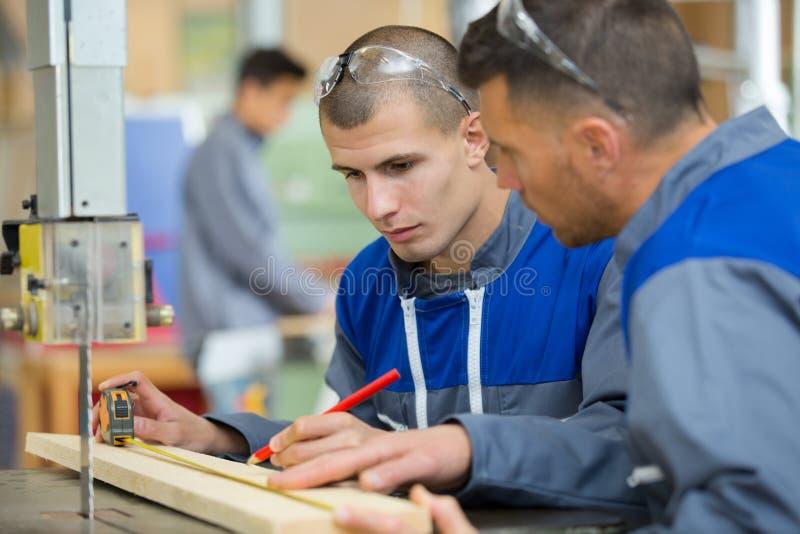 Constructores de sexo masculino de los carpinteros que miden la madera imágenes de archivo libres de regalías