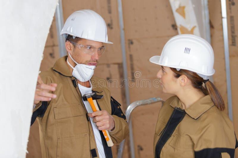 Constructores de sexo masculino y de sexo femenino que hablan en emplazamiento de la obra foto de archivo
