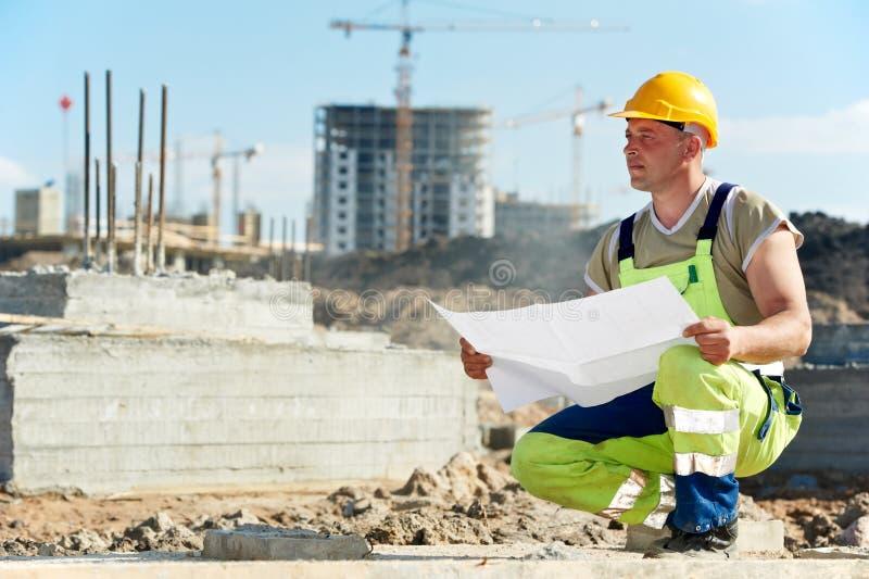 Constructores del ingeniero en el emplazamiento de la obra con el bosquejo imagen de archivo