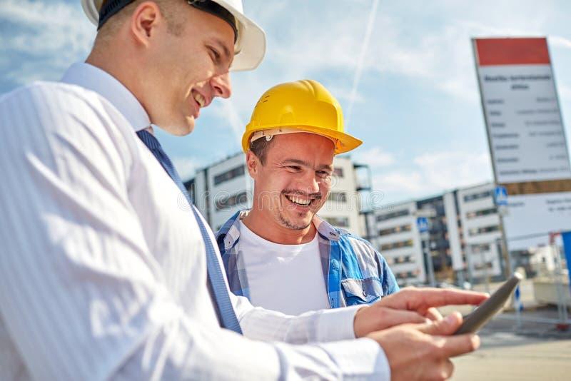Constructores felices en cascos de protección con PC de la tableta al aire libre fotos de archivo libres de regalías