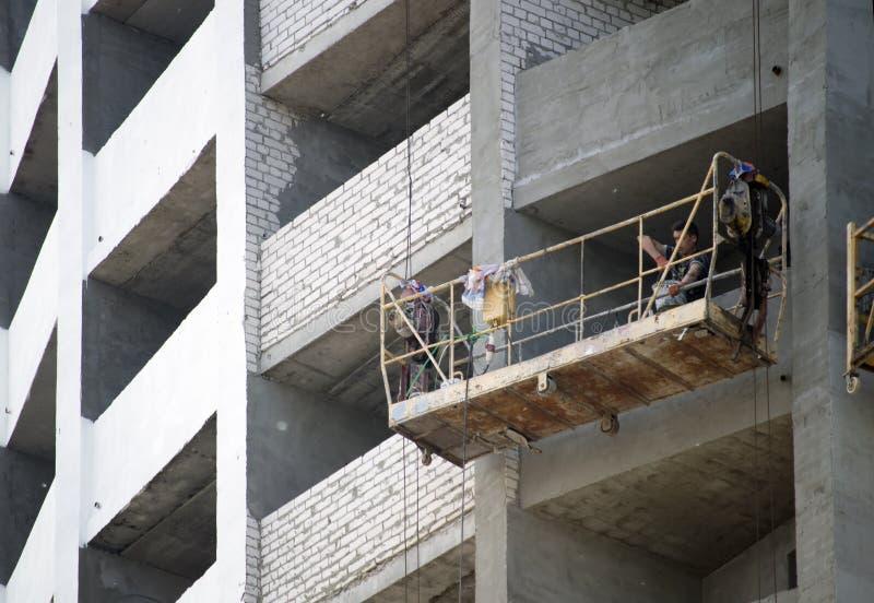 Constructores que trabajan en la construcción de la casa del ladrillo ucrania imagen de archivo libre de regalías