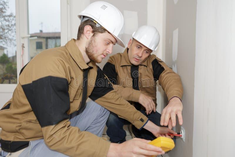 Constructores usando el multímetro amarillo para calibrar la casa fotografía de archivo libre de regalías
