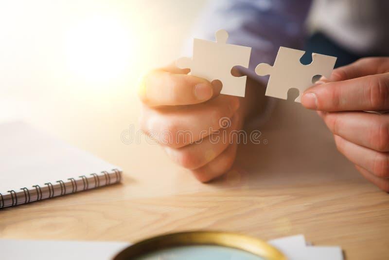 Construindo um sucesso comercial As mãos com enigmas imagens de stock