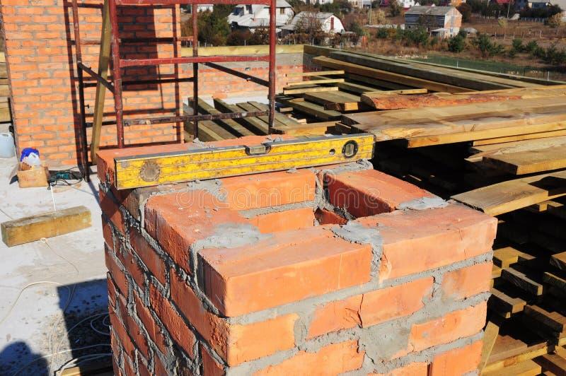 Construindo uma chaminé do tijolo Construção da chaminé da alvenaria - tijolo que coloca o nível de espírito das ferramentas imagens de stock