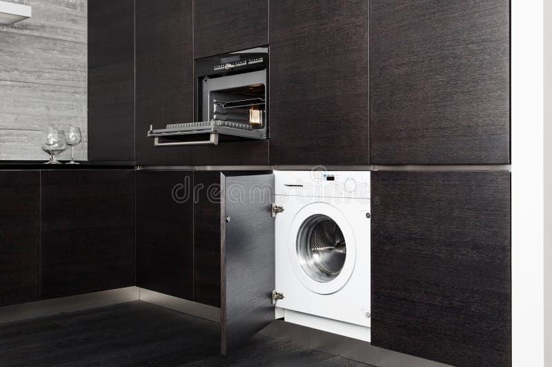 Construir-na máquina de lavar e no fogão na cozinha imagem de stock