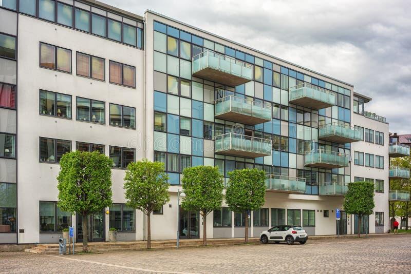 Construisez nouvellement l'immeuble avec des arbres et des parkings de voiture devant lui photographie stock